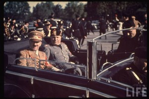 Adolf Hitler & Benito Mussolini riding in limo through streets flanked by black uniformed Italian Fascists; during Hitler's state visit - Location: Florence, Italy - Date taken: May 1938